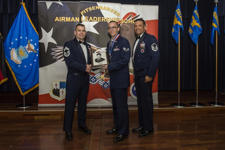 U.S. Air Force Senior Airman Michael Kent, a 726 Air Mobility Squadron client systems technician, middle, receives the John L. Levitow during the Pitsenbarger Airman Leadership School 16-E graduation at Club Eifel on Spangdahlem Air Base, Germany, June 30, 2016. The Levitow award is highest honor given to the student who displays excellence in all categories of ALS. (U.S. Air Force photo by Senior Airman Luke Kitterman/Released)