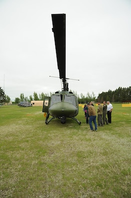 CAVALIER AIR FORCE STATION, N.D. – Open house guests speak with the crew of an UH-1N Huey helicopter on Cavalier Air Force Station, N.D., June 11, 2016. The crew belongs to the 54th Helicopter Squadron from Minot Air Force Base, N.D., and the craft was flown in to support an open house for the local community. (U.S. Air Force photo by Senior Airman Ryan Sparks)