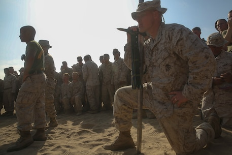 Lieutenant Colonel Michael Nakonieczny, the commanding officer of Headquarters Battalion, 1st Light Armored Reconnaissance Battalion, 1st Marine Division, knees down with the battalion's Highlander Sword while Marines fight using pugil sticks during 1st LAR's Highlander Night aboard Marine Corps Base Camp Pendleton, Calif., June 30, 2016. The Highlander Night tightens the bonds of brotherhood through competitions that pit unit against unit. (U.S. Marine Corps photo by Lance Cpl. Timothy Valero/ Released)
