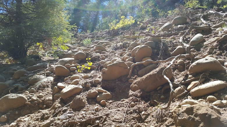 Boulders on an eroding slope above the Chamisal Acequia. Memphis District engineers are designing a solution that will help keep the acequia flowing freely.