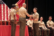 Sgt. Kaitlin Fugate, honor graduate from Sergeant's Course class 14-16, receives an award for excellence among her peers during the course graduation at the base theater on Marine Corps Base Camp Lejeune June 10. Sergeant's Course is one of many formal professional military education courses run by the Staff Noncommissioned Officer Academy to enhance the overall Marine, who in turn can give back to their units. (U.S. Marine Corps photo by Cpl. Mark Watola /released)