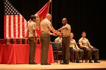 Sgt. Ricky Hassan, gung ho recipient from Sergeant's Course class 14-16, receives an award for excellence among his peers during the course graduation at the Base Theater on Marine Corps Base Camp Lejeune June 10. Sergeant's Course is one of many formal professional military education courses run by the Staff Noncommissioned Officer Academy to enhance the overall Marine, who in turn can give back to their units. (U.S. Marine Corps photo by Cpl. Mark Watola /Released)