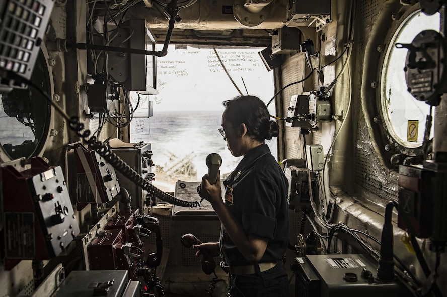 Navy Lt. j.g. Catherine Miller stands watch inside the helicopter control tower on the USS San Jacinto.