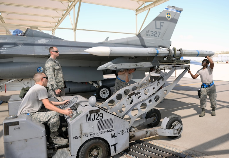 A weapons load crew from the 309th Aircraft Maintenance Unit loads an inert AIM-120 air-to-air missile onto an F-16 during the annual Second Quarter Load Crew Competition July 1, 2016, at Luke Air Force Base. The competition pitted teams from different AMUs against each other in a race to complete the loading of weapons onto either an F-16 or an F-35 first. (U.S. Air Force photo by Airman 1st Class Ridge Shan)