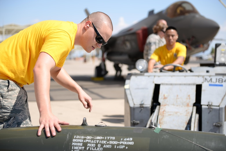 Staff Sgt. Mark Beyer, 61st Aircraft Maintenance Unit load crew leader, and Airman 1st Class Theodore Reyes, 61st AMU load crew member, prepare an inert bomb for loading onto an F-35 during the annual Second Quarter Load Crew Competition July 1, 2016, at Luke Air Force Base, Ariz. The competition pitted teams from different AMUs against each other in a race to complete the loading of weapons onto either an F-16 or an F-35 first. (U.S. Air Force photo by Airman 1st Class Ridge Shan)