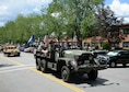 Parade participants smile and wave from a vintage military vehicle during a Heroes Homecoming celebration on base July 23, 2015. Hanscom personnel are invited to help welcome home more than 60 service members who have returned from deployment in the past year during the 2016 celebration to be held July 21. (U.S Air Force photo by Linda LaBonte Britt)