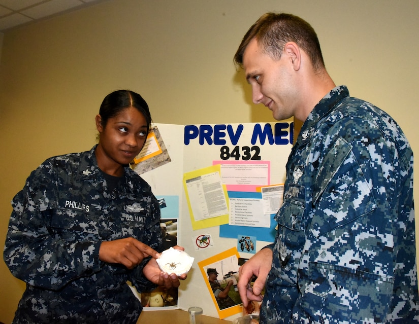 Petty Officer 1st Class Shamace Phillips, a preventive medicine technician serving at Naval Health Clinic Charleston, exhibits a specimen of a spider native to the Lowcountry to Petty Officer 3rd Class Brent Smith, a general duty corpsman serving in Military Medicine at NHCC, during NHCC's Navy Enlisted Classification Fair June 29, 2016. One of the many duties of the preventive medicine technician is to collect and study insects in the local area for disease prevention. During the NEC Fair, Phillips was one of many representatives from NHCC who staffed tables filled with interactive displays and information about the Hospital Corps, Hospital Corps classifications and various programs available to enlisted Sailors. (Navy photo by Kris Patterson)