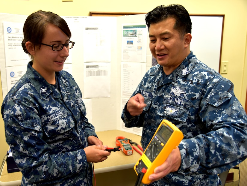 Petty Officer 2nd Class Dien Pham, a biomedical equipment technician serving at Naval Health Clinic Charleston, demonstrates the different functions of a multi-meter to Petty Officer 3rd Class Whitney Nielsen, an NHCC lab technician, June 29, 2016 at NHCC's Navy Enlisted Classification Fair. Biomedical equipment technicians troubleshoot and repair medical equipment. During the NEC Fair, the BET career field was showcased among many Hospital Corps rates, or specialties. (Navy photo by Kris Patterson)