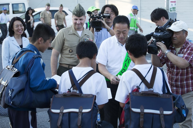 The Honorable Yoshihiko Fukuda, mayor of Iwakuni, right, hands out fliers to local Japanese students while walking with U.S. Marine Corps Col. Robert V. Boucher, commanding officer of Marine Corps Air Station Iwakuni, during the seventh Joint Leadership Walk down the streets of Iwakuni on July 6, 2016. The last walk took place in December 2015 and continues to be a firm demonstration of the bond and unity between both communities. (U.S. Marine Corps photo by Lance Cpl. Donato Maffin/Released