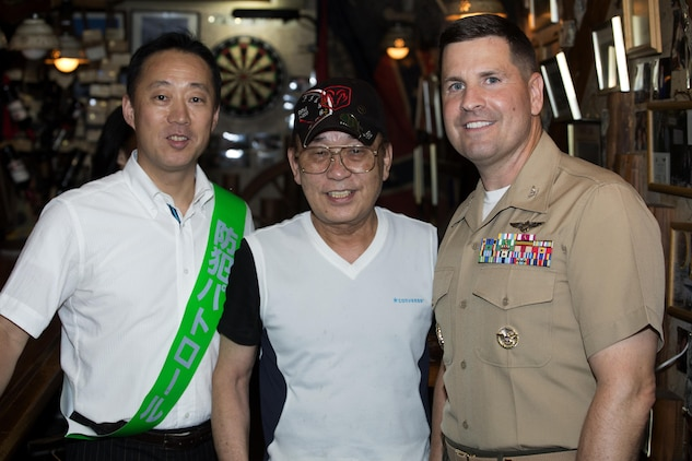 The Honorable Yoshihiko Fukuda, mayor of Iwakuni, Japan, left, and U.S. Marine Corps Col. Robert V. Boucher, commanding officer of Marine Corps Air Station Iwakuni, pose for a photo with Eddie M. Nagamine, a store owner, during the seventh Joint Leadership Walk down the streets of Iwakuni on July 6, 2016. The last walk took place in December 2015 and continues to be a firm demonstration of the bond and unity between both communities. (U.S. Marine Corps photo by Lance Cpl. Donato Maffin/Released)