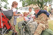 "Spc. William Meeks, a medic with Headquarters and Headquarters Company, 1st Battalion, 18th Infantry Regiment, 2nd Armored Brigade Combat Team, 1st Infantry Division, gives gifts to his daughters Alexis, Daniel and Olivia after a homecoming ceremony June 25 at Fort Riley. Meeks returned with about 250 other Soldiers from the 2nd ABCT after a nine-month deployment. The ""Dagger"" brigade Soldiers supported stability and security in the Southwest Asia region."