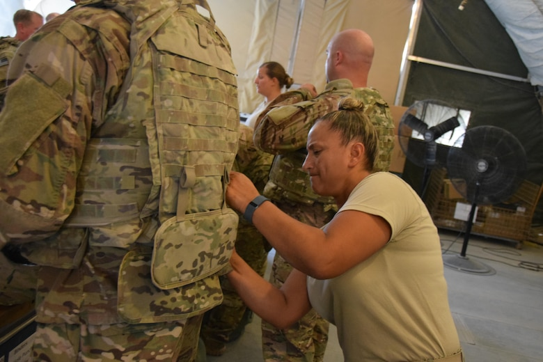Getting the right fit is important when fitting protective equipment onto service members going downrange according to Master Sgt. Michelle Guida, Expeditionary Theater Distrbution Center superintendant, as she adjusts body armor to a customer June 23, 2016 at Al Udeid Air Base, Qatar.  The ETDC is part of the 379th Logistics Readiness Squadron, and is the busiest one in the Air Force Guida said. (U.S. Air Force photo by Technical Sgt. Carlos J. Trevino/Released)