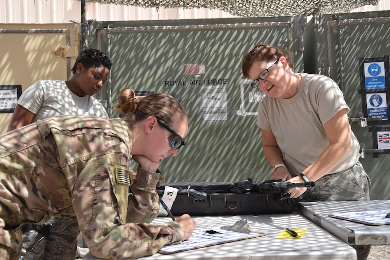 Senior Airman Devondra Randall, armory journeyman (left) and Master Sgt. Suzanne McMurray, NCO in charge transient armory, assist Technical Sgt. Jennifer Brandt June 23, 2016 at Al Udeid Air Base, Qatar.  Brandt, a personnelist on her way downrange, had to turn in her weapons and complete paperwork as she made a planned stop. (U.S. Air Force photo/Technical Sgt. Carlos J. Trevino/Released)