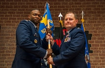 U.S. Air Force Col. Alfred Flowers, 52nd Medical Group commander, left, takes the ceremonial guidon from U.S. Air Force Lt. Col. Wade Adair, outgoing 52nd Medical Support Squadron commander, during the 52nd MDSS change of command ceremony in the Brickhouse on Spangdahlem Air Base, Germany, June 30, 2016. The guidon symbolized the authority Flowers placed on Adair, who then relinquished command over the 52nd MDSS as the flag exchanged hands. (U.S. Air Force photo by Airman 1st Class Timothy Kim/Released)