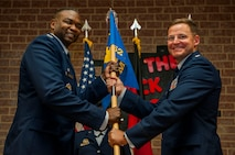 U.S. Air Force Col. Alfred Flowers, 52nd Medical Group commander, left, gives the ceremonial guidon to U.S. Air Force Lt. Col. Thomas Lesnick, incoming 52nd Medical Support Squadron commander, during the 52nd MDSS change of command ceremony in the Brickhouse on Spangdahlem Air Base, Germany, June 30, 2016. Lesnick assumed command from U.S. Air Force Lt. Col. Wade Adair, outgoing 52nd MDSS commander, under the overseeing authority of Flowers and formally greeted his new squadron for the first time during the ceremony. (U.S. Air Force photo by Airman 1st Class Timothy Kim/Released)