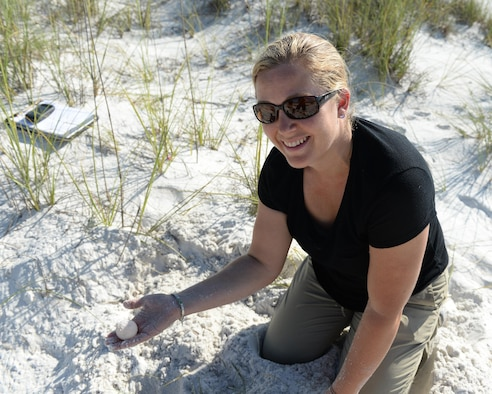 Danielle Bumgardner, 325th Civil Engineer Squadron Environmental Flight biologist, finds a turtle egg at Tyndall Air Force Base, Fla., June 22, 2016. Onshore threats to eggs and hatchlings include ghost crabs, coyotes, raccoons, opossums, dogs, feral cats, seagulls, wading birds, crows, eagles and egg poachers. Biologists like Bumgardner find and protect the turtle nests to ensure the hatchlings have a chance to make it to adulthood. (U.S. Air Force photo by Airman 1st Class Cody R. Miller/Released)