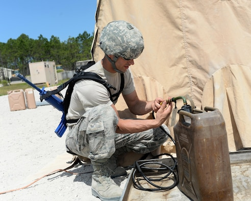 U.S. Air Force Senior Airman Casey Belieu, 104th Fighter Wing services specialist, Barnes Air National Guard Base, Westfield, Mass., connects a fuel tank to a tent-covered kitchen at the Silver Flag exercise site at Tyndall Air Force Base, Fla., June 23, 2016. Services specialists from the 104th came to the Silver Flag site to learn how to conduct their duties in a deployed environment. (U.S. Air Force photo by Airman 1st Class Cody R. Miller/Released)