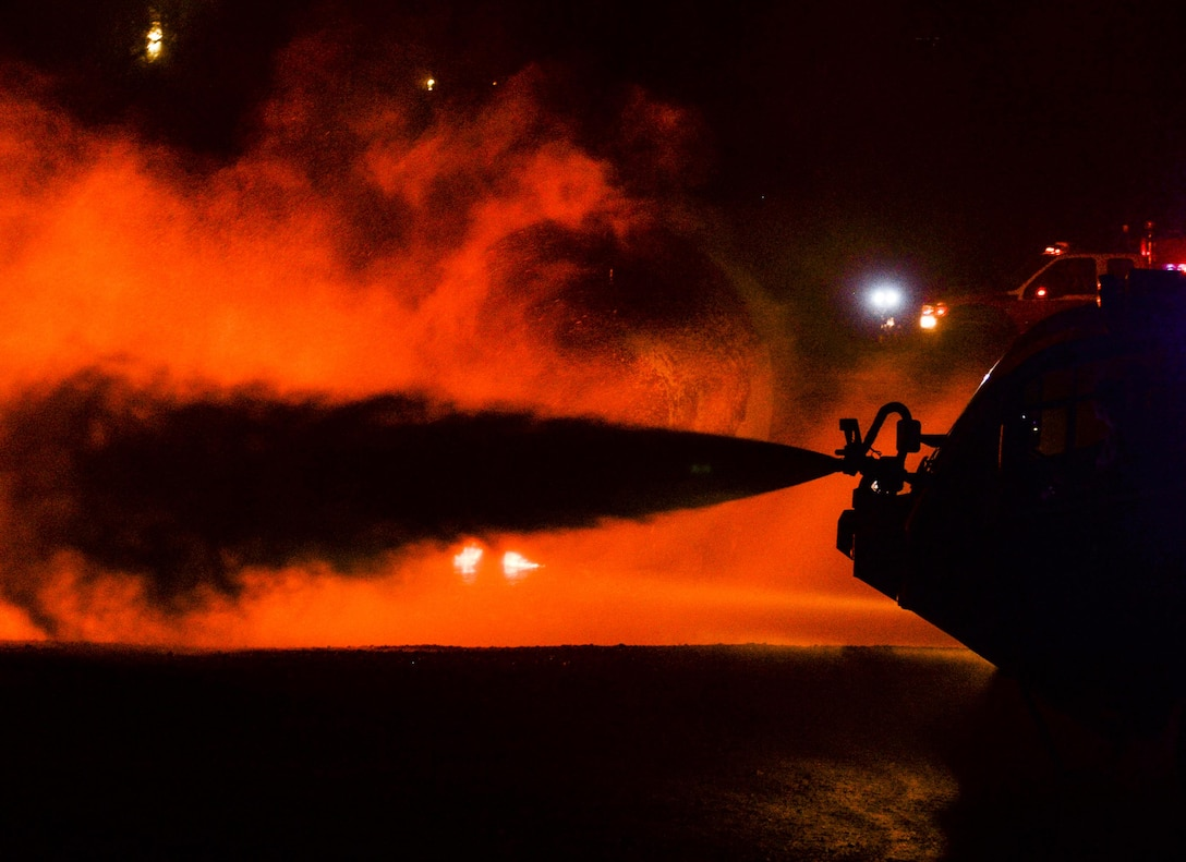 U.S. Air Force firefighters douse the flames of a burning aircraft husk during a burn pit training exercise at the Silver Flag exercise site at Tyndall Air Force Base, Fla., June 23, 2016. During the seven-day Silver Flag course, firefighters receive specific expeditionary training that supplies the combatant commander with a highly trained and skilled emergency response force. (U.S. Air Force photo by Airman 1st Class Cody R. Miller/Released)