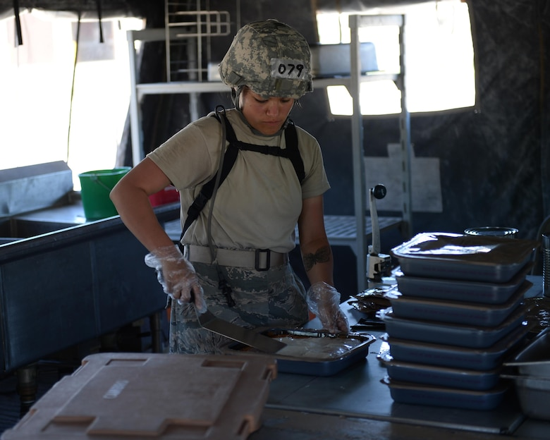 U.S. Air Force Airman 1st Class Nicolle Vella, 104th Fighter Wing services specialist, prepares food for students at the Silver Flag exercise site at Tyndall Air Force Base, Fla., June 23, 2016. The services students are from Barnes Air National Guard Base, Mass., and were tasked with setting up a working kitchen on-site and providing freshly made food for all the students going through the course. (U.S. Air Force photo by Airman 1st Class Cody R. Miller/Released)