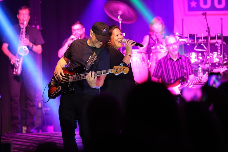 Gary Sinise and Mari Anne Jayme stand back-to-back as they perform on the Two Rivers Theater stage at Marine Corps Air Station Cherry Point, N.C., July 5, 2016. Gary Sinise and the Lt. Dan Band have participated in 70 United Service Organization tours since they came together. In total, they have entertained more than 363,000 service members and military families in 13 countries. The band puts on shows to raise spirits, funds and awareness for severely wounded warriors in need. Sinise plays the elecric bass and Jayme is a vocalist with the Lt. Dan Band. (U.S. Marine Corps photo by Lance Cpl. Mackenzie Gibson/Released)