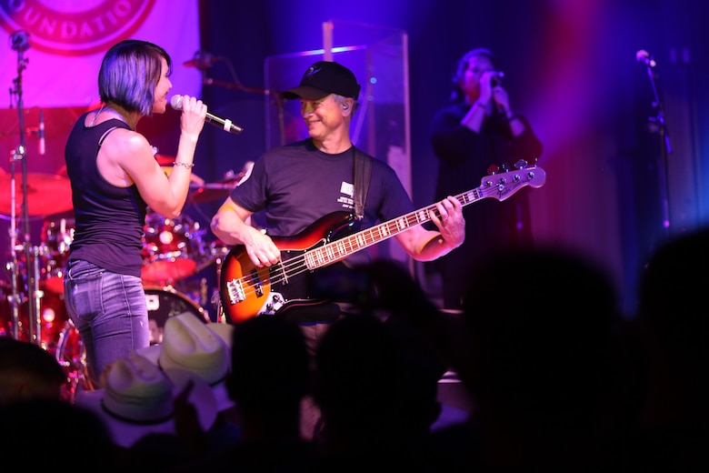 Molly Callinan (left) and Gary Sinise perform a song on the Two Rivers Theater stage at Marine Corps Air Station Cherry Point, N.C., July 5, 2016. Gary Sinise and the Lt. Dan Band have participated in 70 United Service Organization tours since they came together. In total, they have entertained more than 363,000 service members and military families in 13 countries. The band puts on shows to raise spirits, funds and awareness for severely wounded warriors in need. Callinan is a vocalist and Sinise is a electric bass player with the Lt. Dan Band. (U.S. Marine Corps photo by Lance Cpl. Mackenzie Gibson/Released)