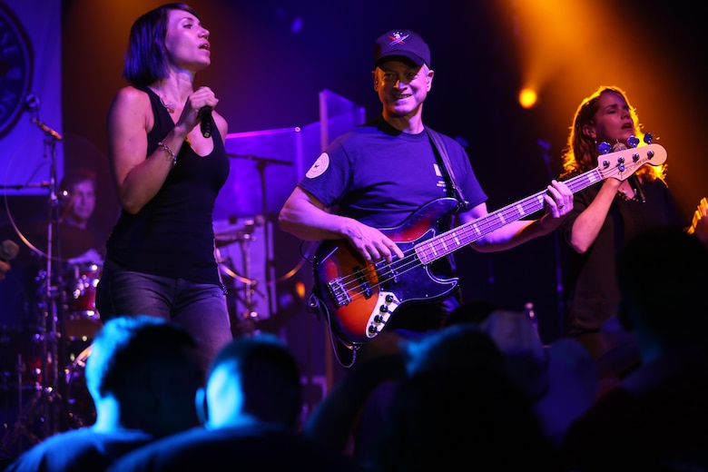 Molly Callinan (left) and Gary Sinise perform for a roaring crowd during a performance on the Two Rivers Theater stage at Marine Corps Air Station Cherry Point, N.C., July 5, 2016. Gary Sinise and the Lt. Dan Band have participated in 70 United Service Organization tours since they came together. In total, they have entertained more than 363,000 service members and military families in 13 countries. The band puts on shows to raise spirits, funds and awareness for severely wounded warriors in need. Callinan is a vocalist and Sinise is a electric bass player with the Lt. Dan Band. (U.S. Marine Corps photo by Lance Cpl. Mackenzie Gibson/Released)