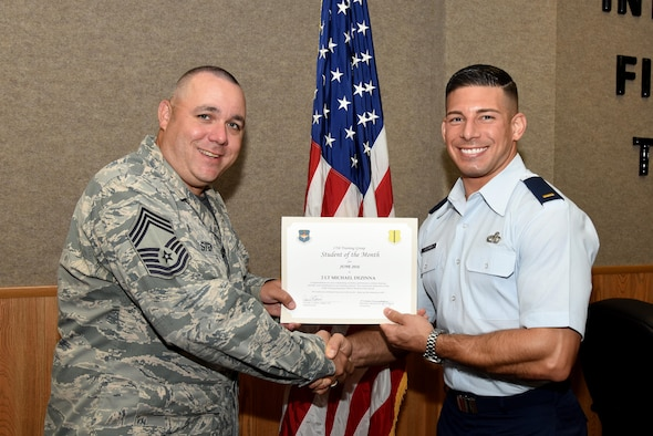 U.S. Air Force Chief Master Sgt. Daniel Stein, 17th Training Group superintendent, presents the 315th Training Squadron Officer Student of the Month award for June 2016 to 2nd Lt. Michael Dezinna in Brandenburg Hall on Goodfellow Air Force Base, Texas, July 1, 2016. (U.S. Air Force photo by Senior Airman Joshua Edwards/Released)