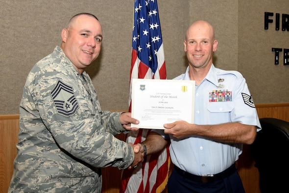U.S. Air Force Chief Master Sgt. Daniel Stein, 17th Training Group superintendent, presents the 312th Training Squadron Student of the Month award for June 2016 to Tech. Sgt. Drew Layson in Brandenburg Hall on Goodfellow Air Force Base, Texas, July 1, 2016. (U.S. Air Force photo by Senior Airman Joshua Edwards/Released)