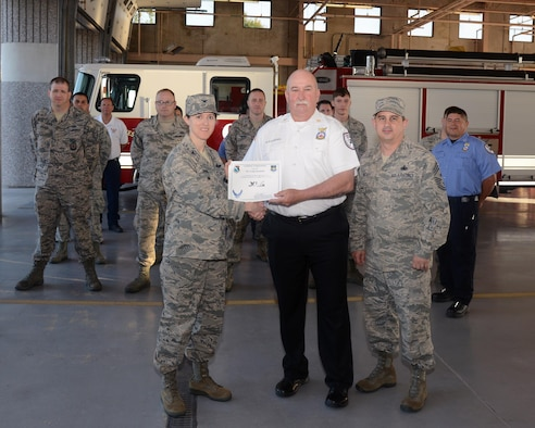 """Craig Alexander, 47th Civil Engineer Squadron fire department health and safety assistant chief, accepts the """"XLer of the Week"""" award from Col. Michelle Pryor, left, 47th Flying Training Wing vice commander, and Chief Master Sgt. George Richey, 47th FTW command chief, here, June 29, 2016. The XLer is a weekly award chosen by wing leadership and is presented to those who consistently make outstanding contributions to their unit and Laughlin. (U.S. Air Force photo/Airman 1st Class Brandon May)"""