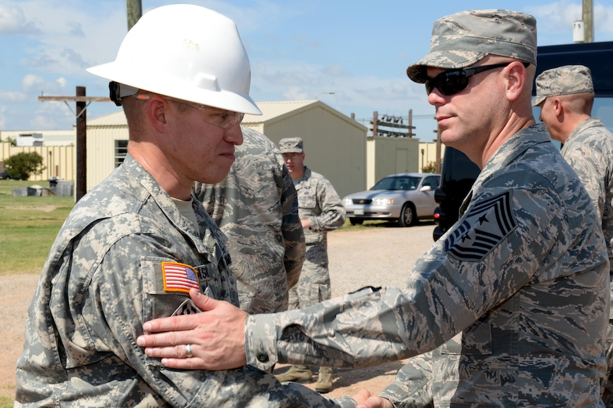 Command Chief Master Sgt. David Staton, Air Education and Training Command, shakes hands with U.S. Army Staff Sgt. Brad Eason, 366th Training Squadron electrical engineer instructor, after a brief course introduction at Sheppard Air Force Base, Texas, June 29, 2016. The chief visited Sheppard for three days for a familiarization tour of its training mission and capabilities.