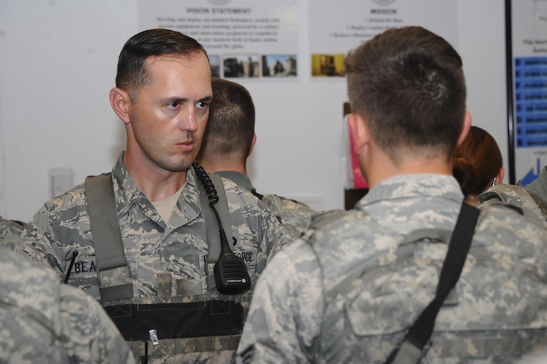 U.S. Air Force Master Sgt. David Beasley, 355th Security Forces Squadron trainer, checks an Airman's dress and appearance during open ranks at Davis-Monthan Air Force Base, Ariz., July 7th, 2016. Security Forces members are responsible for ensuring the safety of base weapons, property and personnel from hostile forces. (U.S. Air Force photo by Airman 1st Class Mya M. Crosby/Released)