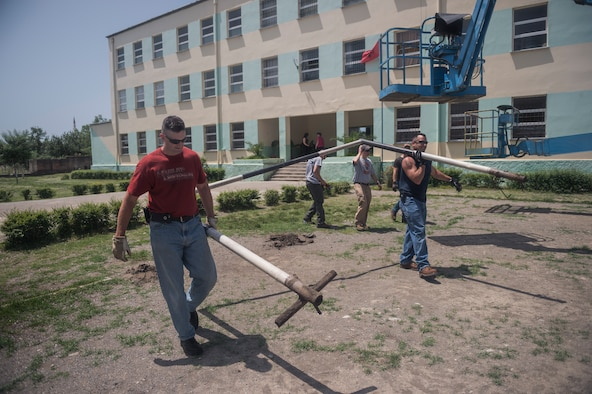 Soccer goal posts are removed from the local school in Mjede, Albania, to be reused for a new soccer field that Airmen from the 107th Civil Engineer Squadron, Niagara Falls Air Reserve Station, N.Y., are preparing during June 18-July 2, 2016. The Airmen did such work as cleaning up the grounds, replacing windows and painting as part of a Deployment For Training. (U.S. Air Force Photo by Staff Sgt. Ryan Campbell/Released)