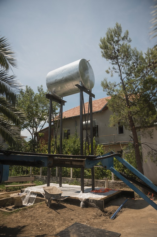 Airmen from the 107th Civil Engineer Squadron, Niagara Falls Air Reserve Station, N.Y., engineer a support structure to mount a 5,000 liter water tank to in order to ensure the clinic in Vau Dejes, Albania, always has a source of running water, June 18-July 2, 2016. The Airmen did such renovations as replacing walls, windows and doors as part of a Deployment For Training. (U.S. Air Force Photo by Staff Sgt. Ryan Campbell/released)