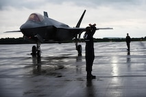 An Airman with the Air Combat Command F-35A Heritage Flight team marshals an F-35A Lightning II to its parking spot on the flightline at Royal Air Force Fairford, England, June 30, 2016. The team flew to England for the Royal International Air Tattoo. (U.S. Air Force photo/Tech. Sgt. Jarad A. Denton)