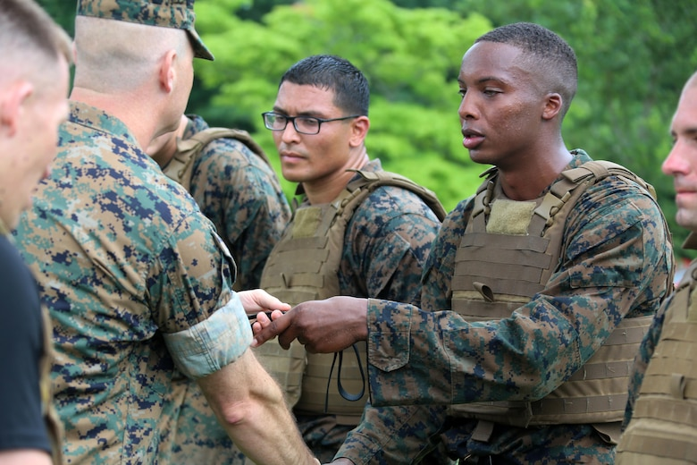 Cpl. Duane Levy, right, receives his Marine Corps Martial Arts instructor belt from Lt. Col. Bret Hyla after completing the four-and-a-half mile endurance course of a MCMAI Course at Marine Corps Air Station Cherry Point, N.C., July 1, 2016. The endurance course was the culminating event of three weeks of physical, mental, and character challenges Marines assigned to MWCS-28 completed to earn their instructor tabs. MCMAP is a combat system that trains Marines in the art of hand-to-hand and close quarters combat techniques while building morale and team-building functions. This MCMAP instructor course was conducted by the unit to certify Marines with the responsibility of instructing and training Marines in MCMAP. MWCS-28 is one of the squadrons assigned to Marine Air Control Group 28, 2nd Marine Aircraft Wing. (U.S. Marine Corps photo by Cpl. N.W. Huertas/Released)
