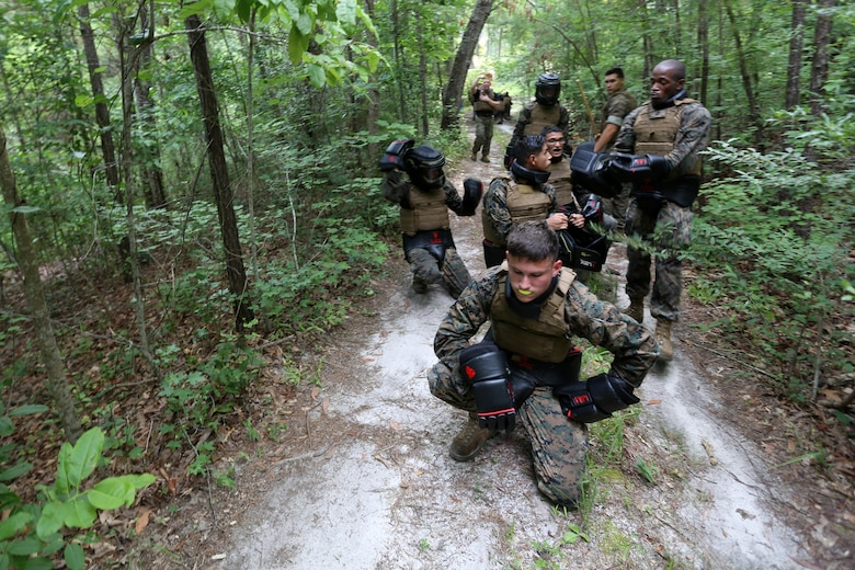 Marines with Marine Wing Communication Squadron 28 adjust their gear prior to an exercise during the four-and-a-half mile endurance course of a Marine Corps Martial Arts Instructor Course at Marine Corps Air Station Cherry Point, N.C., July 1, 2016. The endurance course was the culminating event of three weeks of physical, mental, and character challenges Marines assigned to MWCS-28 completed to earn their instructor tabs. MCMAP is a combat system that trains Marines in the art of hand-to-hand and close quarters combat techniques while building morale and team-building functions. This MCMAP instructor course was conducted by the unit to certify Marines with the responsibility of instructing and training Marines in MCMAP. (U.S. Marine Corps photo by Cpl. N.W. Huertas/Released)