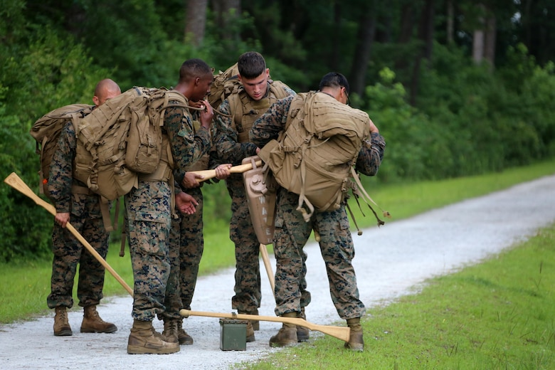 Marines with Marine Wing Communication Squadron 28 gather their gear during the four-and-a-half mile endurance course of a Marine Corps Martial Arts Instructor Course at Marine Corps Air Station Cherry Point, N.C., July 1, 2016. The endurance course was the culminating event of three weeks of physical, mental, and character challenges Marines assigned to MWCS-28 completed to earn their instructor tabs. MCMAP is a combat system that trains Marines in the art of hand-to-hand and close quarters combat techniques while building morale and teamwork. This MCMAP instructor course was conducted by the unit to certify Marines with the responsibility of instructing and training Marines in MCMAP. MWCS-28 is one of the squadrons assigned to Marine Air Control Group 28, 2nd Marine Aircraft Wing (U.S. Marine Corps photo by Cpl. N.W. Huertas/Released)
