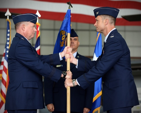 U.S. Air Force Maj. Gen. Eugene Haase, Air Force Special Operations Command vice commander passes the guidon to U.S. Air Force Col. Matthew Smith, 352nd Special Operations Wing incoming commander during the 352 SOW change of command ceremony July 8, 2016, on RAF Mildenhall, England. Smith took command of the 352nd SOW following U.S. Air Force Col. William Holt's departure as part of routine military assignment rotations. (U.S. Air Force photo by Senior Airman Christine Halan/Released)