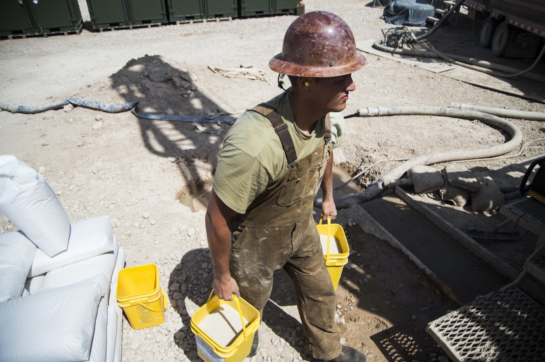 Staff Sgt. Donald Fisher, a well drilling technician assigned to the 557th Expeditionary Red Horse Squadron, carries buckets of sand to pour down the well site at Al Taqaddum Air Base, Iraq, June 2, 2016. The 557th ERHS well drilling team are obtaining an organic water source for Al Taqaddum. Red Horse is helping to improve Iraq's infrastructure in support of the Government of Iraq. (U.S. Air Force photo/Staff Sgt. Larry E. Reid Jr., Released)