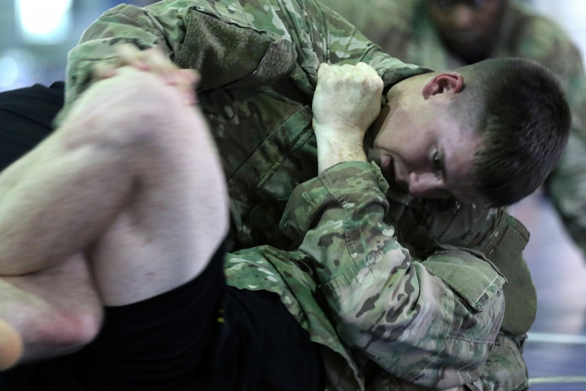 Spc. Joe Lucchesi, a Newburgh, N.Y. resident, moves into side control during a U.S. Army Combatives Level I class July 1 at Camp Arifjan, Kuwait. Lucchesi finished the class as the honor graduate after defeating two fellow classmates for the top honor.