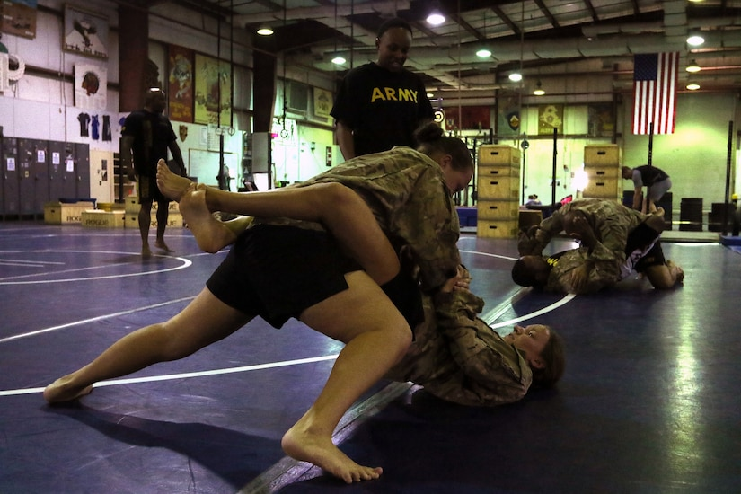 1st Lt. Rebecca Tracy (bottom), holds Spc. Leeza Pike, both Soldiers from the 10th Combat Support Hospital, in her guard during the final day of U.S. Army Combatives Level I training July 1 at Camp Arifjan, Kuwait. The class is a 40-hour course in the basics of hand-to-hand combat.