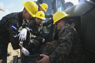 Corporal Kaleb R. Hougland, senior heavy equipment mechanic, conducts a period of instruction on the maintenance of a Caterpillar D6K Bulldozer at Puerto Castilla, Honduras, June 24, 2016. The Marines worked side-by-side on different construction and restoration projects, and shared knowledge and experience on techniques including maintenance and operation of heavy equipment. (U.S Marine Corps Photo by Cpl. Ian Ferro/Released)