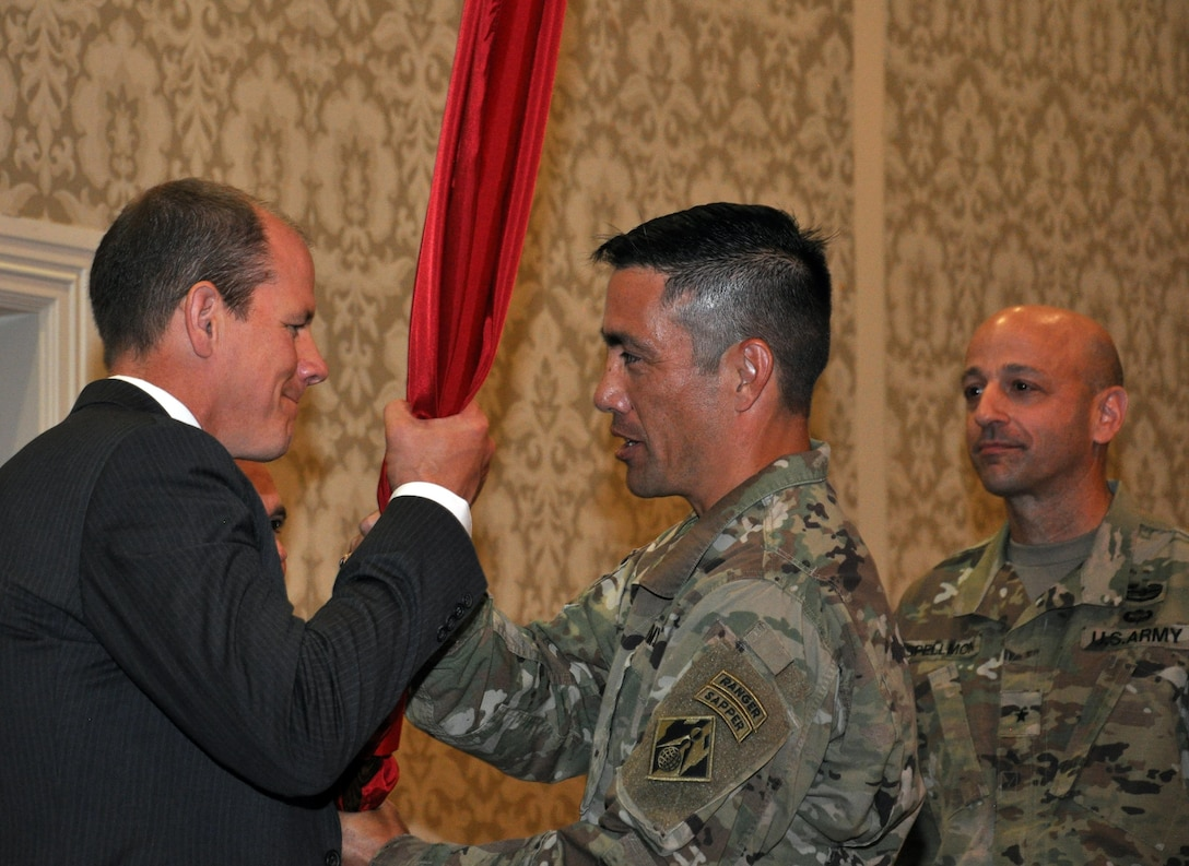 Alan W. Feistner (left), deputy district engineer for project management and chief of Planning, Programs and Project Management Division, receives the Corps colors from Lt. Col. Damon A. Delarosa (middle), Walla Walla District's new commander. Delarosa assumed command of the U.S. Army Corps of Engineers, Walla Walla District, during a July 8, 2016, ceremony at the Marcus Whitman Hotel and Conference Center in downtown Walla Walla. Brig. Gen. Scott A. Spellmon (right), commander of the Corps' Northwestern Division, presided over the ceremony. (U.S. Corps of Engineers photo)