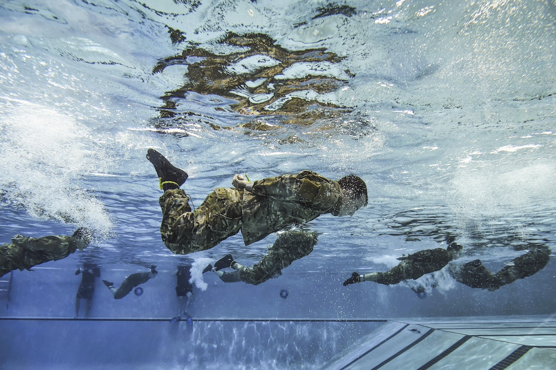 Air Force special tactics students swim the length of the pool with their hands and feet bound during a class before scuba training at Hurlburt Field, Fla., June 29, 2016. The class familiarizes trainees with the basics of water operations. The trainees perform tasks such as tying knots underwater, staying afloat without their arms and hands, and using snorkeling gear. Air Force photo by Senior Airman Ryan Conroy