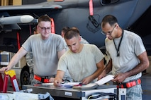 Staff Sgt. Jose Lasanta-Falcon (right), 4th Aircraft Maintenance Squadron load crew team chief, completes final checks while Airman 1st Class Dorian Estrella (center) and Taylor Stevenson (left), 4th AMXS load crew members, look on during a Load Crew of the Quarter competition, July 7, 2016, at Seymour Johnson Air Force Base, North Carolina. Crews of three Airmen from each aircraft maintenance unit on base competed against each other for the best time while ensuring accuracy, serviceability and efficiency. (U.S. Air Force photo/Airman Shawna L. Keyes)