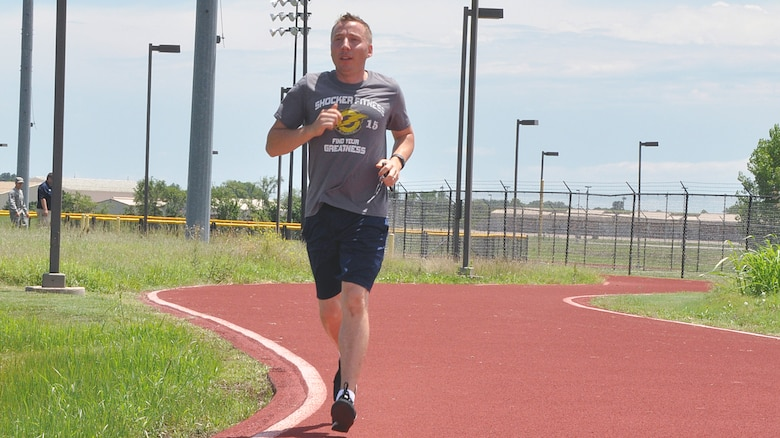 Maj. Brian Doom, 18th Air Refueling Squadron assistant director of operations, runs along the outdoor track July 8, 2016, McConnell Air Force Base, Kansas. Doom often spends his lunch breaks performing physical training to maintain his fitness levels. (U.S. Air Force photo by Senior Airman Preston Webb)