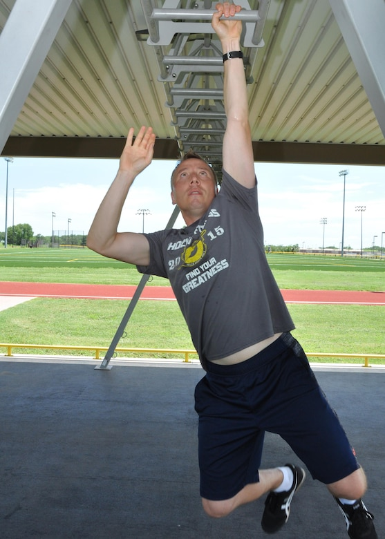 Maj. Brian Doom, 18th Air Refueling Squadron assistant director of operations, climbs along a set of monkey bars July 8, 2016, McConnell Air Force Base, Kansas. Doom used on-base facilities available to McConnell Citizen Airmen to increase his fitness and agility levels to perform in a national fitness competition. (U.S. Air Force photo by Senior Airman Preston Webb)