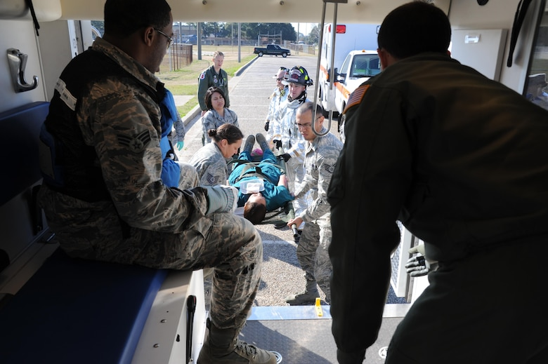 First responders work together to load a simulated victim into an ambulance during a major accident response exercise on the flight line Feb. 12, 2015, on Keesler Air Force Base, Miss. The MARE simulated a C-130J Hercules aircraft crash on base and helped test the agility of Keesler emergency room personnel and first responders. Keesler's emergency room, which is open 24/7, sees around 2,000 patients monthly and is one of several clinics in the medical center. (U.S. Air Force photo by Kemberly Groue/Released)