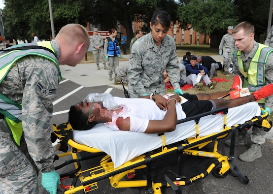 Personnel with the 81st Medical Group prepare a simulated victim to transport to the Keesler Medical Center's emergency room during a chemical, biological, radiological and nuclear exercise scenario, Oct. 22, 2015, on Keesler Air Force Base, Miss. The Force Protection Condition exercise scenario included an intruder simulating releasing gas to cause a mass casualty event. Keesler's emergency room, which is open 24/7, sees around 2,000 patients monthly and is one of several clinics in the medical center. (U.S. Air Force photo by Kemberly Groue/Released)
