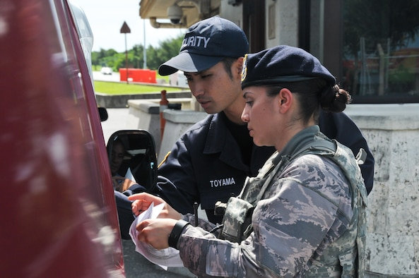 Senior Airman Dominique Castillo (right), 944th Security Forces Squadron member, and Kadena Gate Guard Hiroyuki Toyama, 18th Security Forces Squadron, check a visitor's credentials in order to allow him base access June 28, 2016, at Gate 1 at Kadena Air Base, Okinawa.  A native Arizonian, Castillo has been a Reservist with the 944th for four years and the opportunity to do an off-station annual tour is valuable to her. The 18th Security Forces Squadron capitalized on the extensive experience 944th SFS members brought during their annual tour by seamlessly integrating them into all of their flights. (U.S. Air Force photo by Staff Sgt. Nestor Cruz)